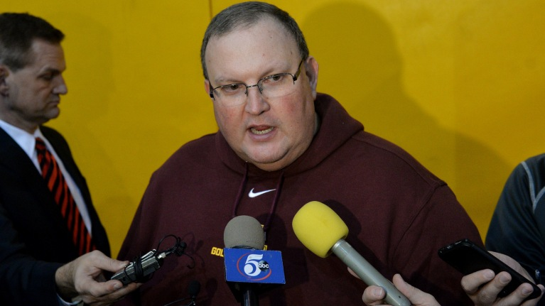 Coach Claeys looking uneasy with three reporter microphones pointed at him.